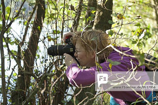 Woman taking photos  Herthasee  Jasmund National Park  Rügen  Mecklenburg-Western Pomerania  Germany  Europe