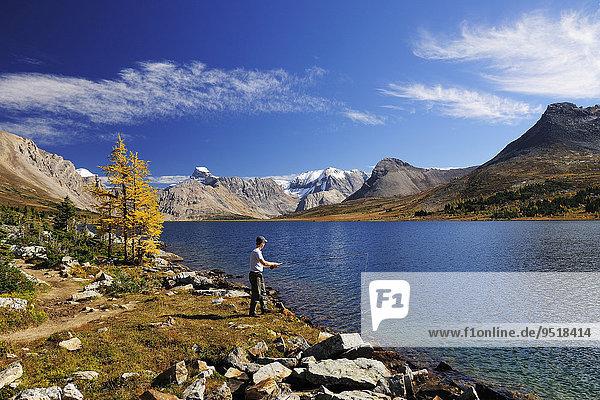 Ein Fischer steht am Ufer des Ptarmigan Lake und angelt  Rocky Mountains  Banff-Nationalpark  Alberta  Kanada  Nordamerika