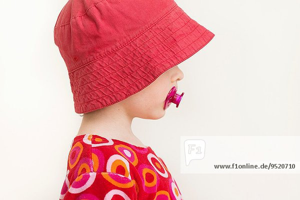 Profile portrait of little girl with red hat and pacifier.
