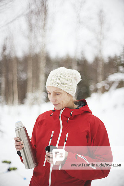 Smiling woman holding thermos