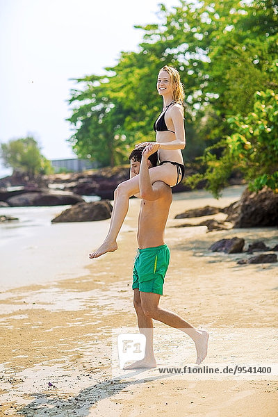 Man carry woman on shoulders on beach