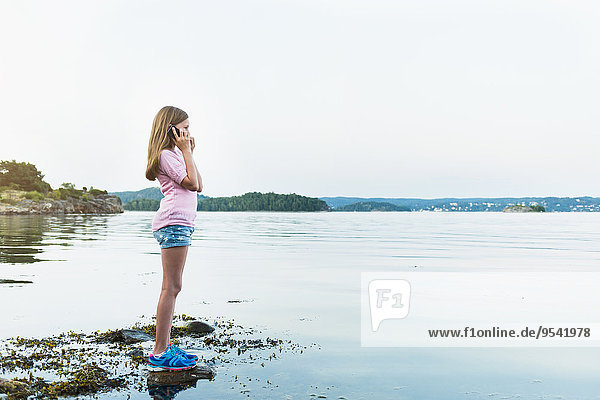 Girl with cell phone at water