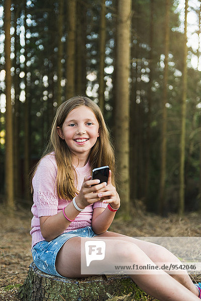 Girl with cell phone at forest