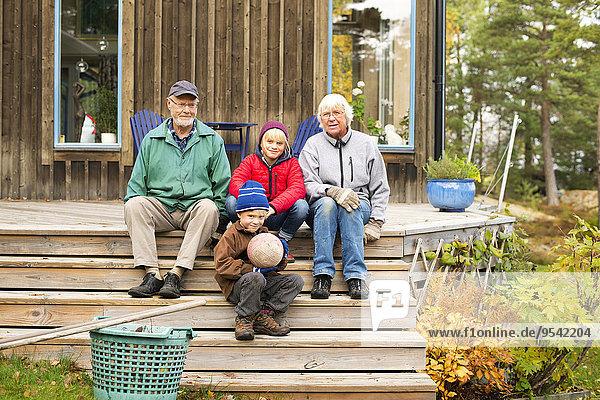 sitzend Wohnhaus frontal Großeltern Enkelkind