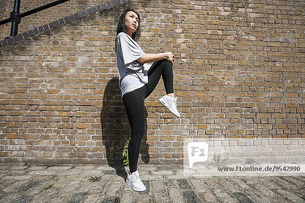 Frau Wand Sport strecken Ziegelstein Ansicht jung Länge Seitenansicht voll