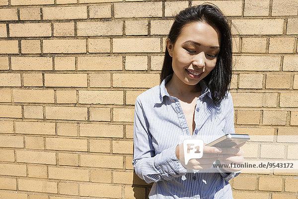 Handy Geschäftsfrau Wand lächeln Ziegelstein Text Kurznachricht jung