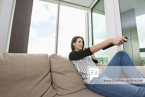 Interior zu Hause junge Frau junge Frauen sehen Couch Fernsehen