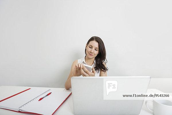 Handy benutzen Geschäftsfrau Schreibtisch Büro jung