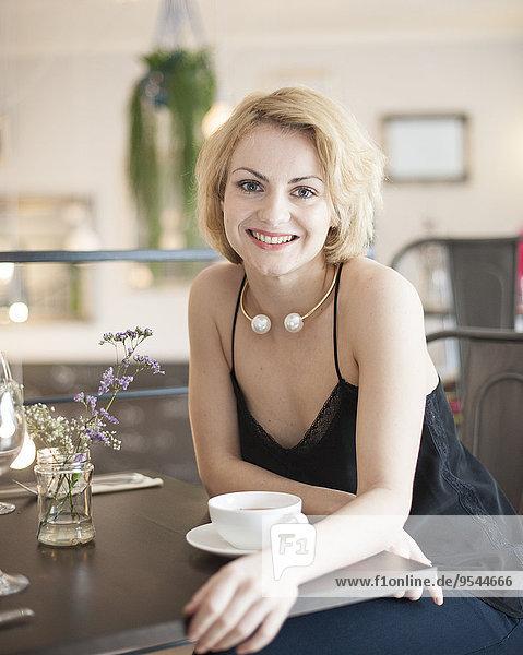 sitzend junge Frau junge Frauen Portrait Fröhlichkeit Restaurant Tisch