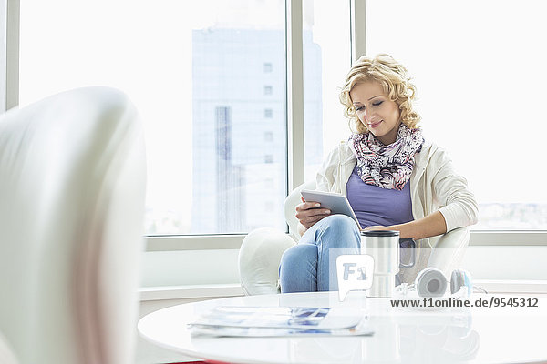 Businesswoman using tablet PC at creative office lobby