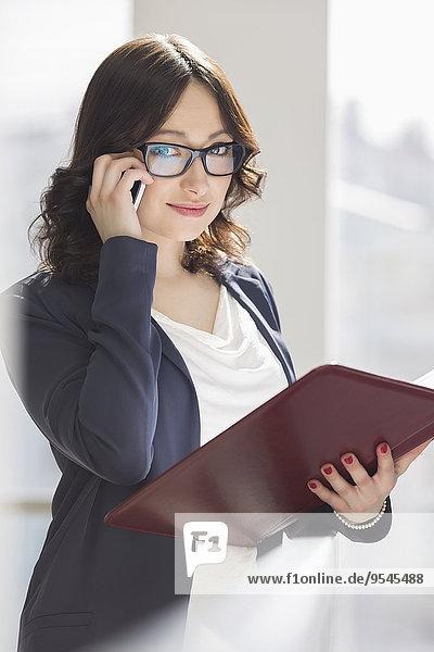 Handy benutzen Portrait Geschäftsfrau lächeln halten Büro Feile