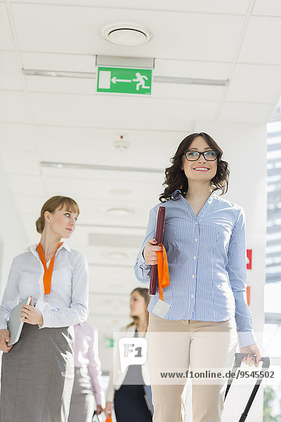 Happy businesswoman pulling luggage while walking with team at airport