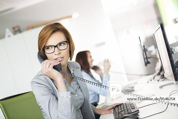 Geschäftsfrau Schreibtisch sprechen Telefon Büro jung