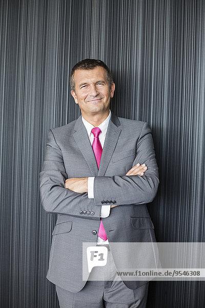 stehend überqueren Portrait Geschäftsmann Wand lächeln reifer Erwachsene reife Erwachsene