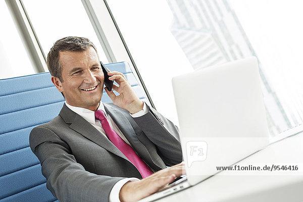 Handy benutzen sprechen Notebook Geschäftsmann lächeln reifer Erwachsene reife Erwachsene Büro
