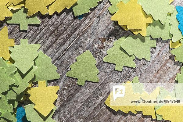 Farbiges Papier in Form von Tannen auf Holz Farbiges Papier in Form von Tannen auf Holz