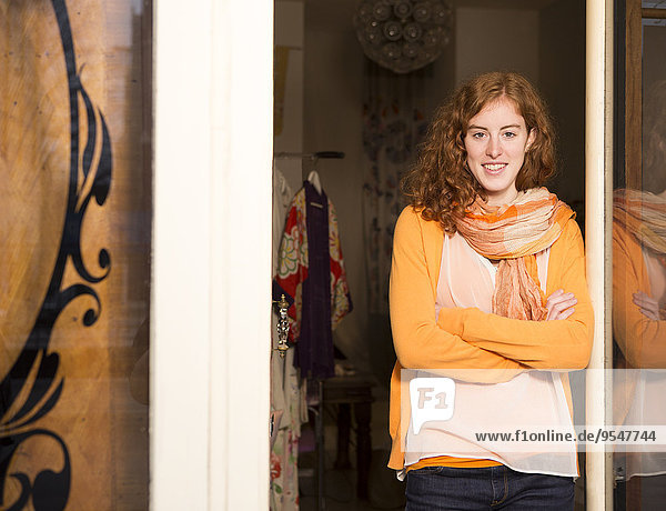 Portrait of female fashion designer standing at the entrance of her studio