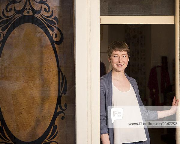Porträt einer Modedesignerin am Eingang ihres Ateliers