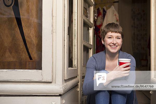 Porträt einer Modedesignerin mit einer Tasse Kaffee am Eingang ihres Ateliers