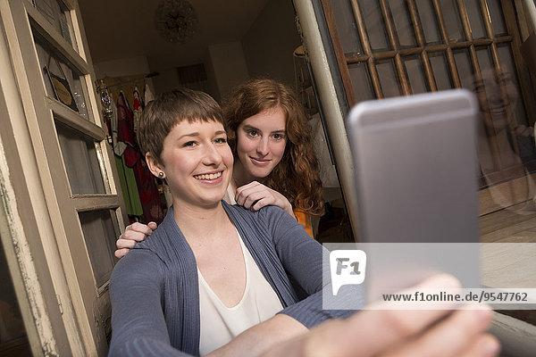 Zwei Modedesignerinnen sitzen am Eingang ihres Studios und nehmen einen Selfie.