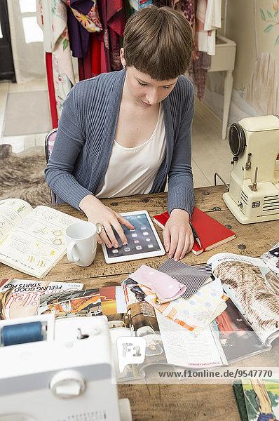 Modedesignerin mit digitalem Tablett am Schreibtisch