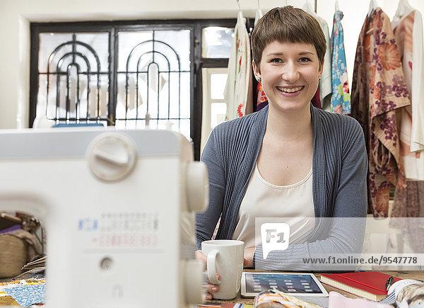 Portrait einer Modedesignerin mit digitalem Tablett am Schreibtisch