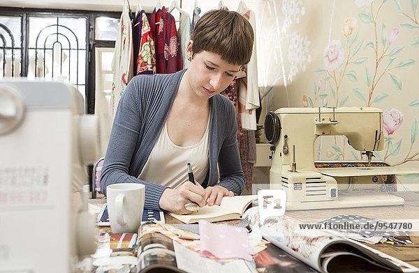 Modedesignerin beim Zeichnen am Schreibtisch