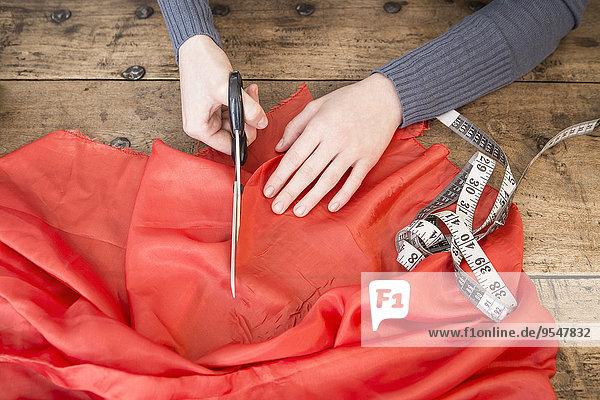 Hände einer jungen Frau  die mit einer Schere rotes Tuch schneidet.
