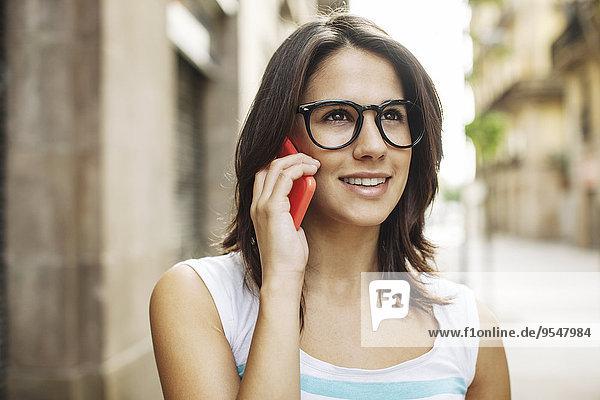 Porträt einer lächelnden jungen Frau beim Telefonieren mit dem Smartphone