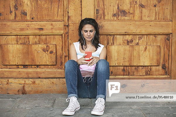 Young woman hearing music with ear phones leaning at wooden door