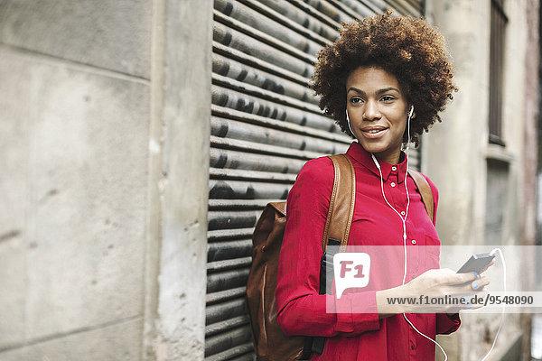 Lächelnde junge Frau hört Musik mit Kopfhörern