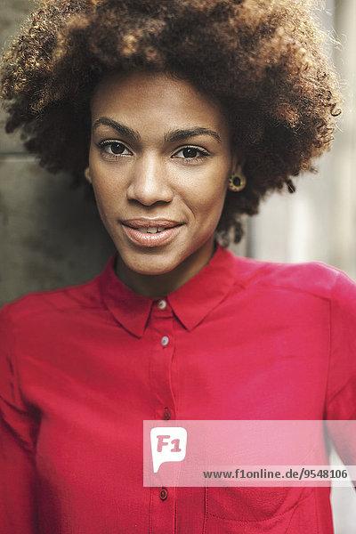Porträt einer lächelnden jungen Frau in roter Bluse