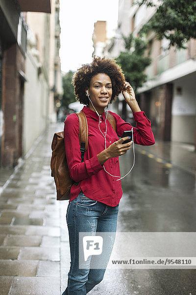 Porträt einer lächelnden jungen Frau  die Musik mit Kopfhörern hört.