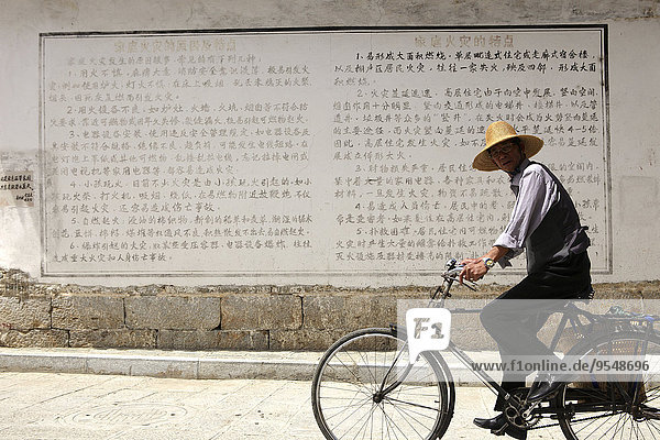 China  Baisha village  man at wall with Chinese script