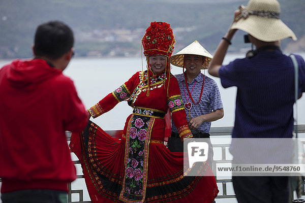 China  Erhai lake  tourists taking pictures of woman in traditional costume