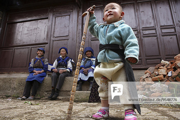 China  Yunnan  Shangri-La County  Lijiang  boy with walking stick in old town