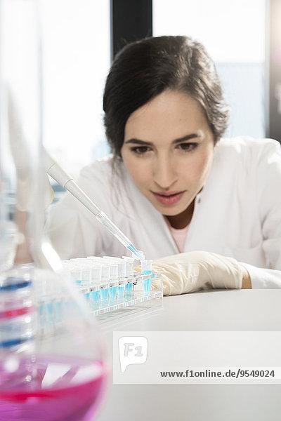 Deutschland,  Berlin,  Forscherin bei der Arbeit mit Reagenzgläsern im Labor