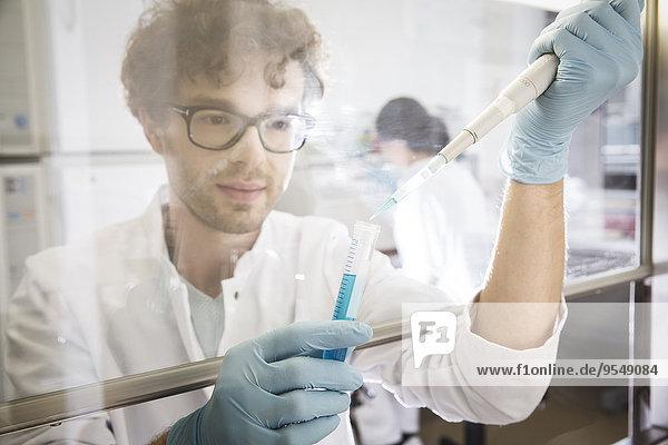 Wissenschaftlerin im Labor  Reagenzglas und Pipette