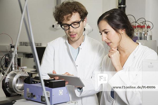 Wissenschaftler  die im analytischen Labor mit Tablettencomputern arbeiten