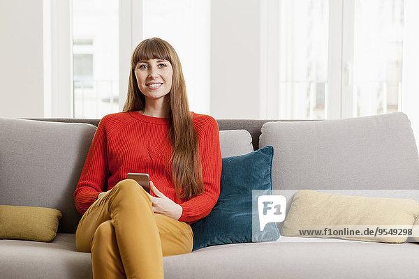 Lächelnde Frau sitzt auf dem Sofa und hält das Handy.