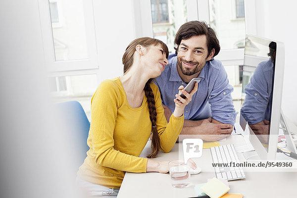 Paar mit Handy am Schreibtisch im Home-Office