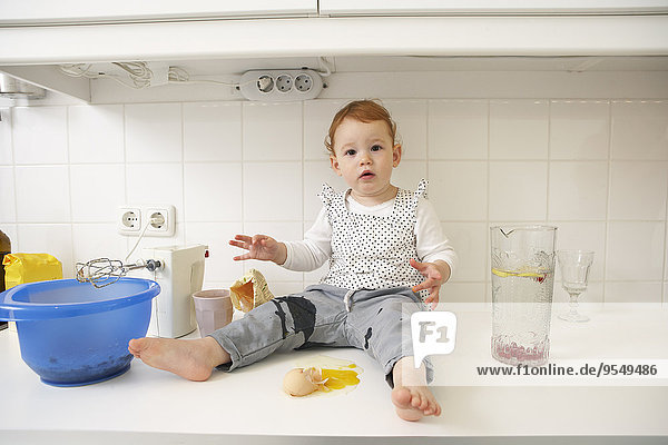 Kleines Mädchen sitzt auf der Küchentheke mit zerbrochenem Ei