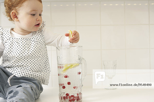 Kleines Mädchen nimmt Zitronenscheiben aus der Wasserkaraffe