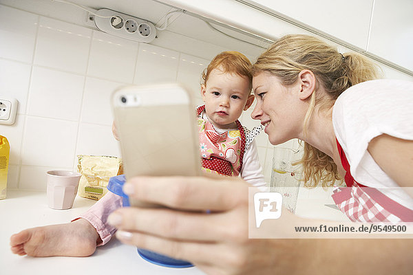 Young woman taking a selfie with her little daughter in their kitchen
