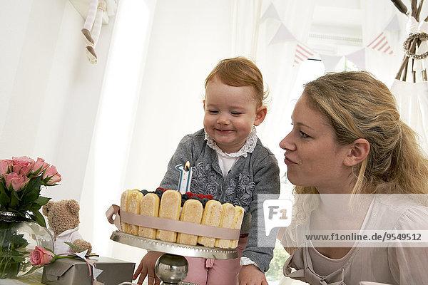 Mutter und Tochter feiern den ersten Geburtstag des kleinen Mädchens mit einem selbstgebackenen Kuchen.