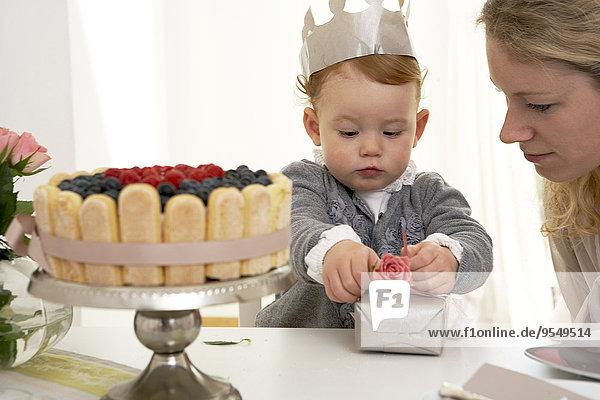 Kleines Mädchen beim Auspacken zum ersten Geburtstag