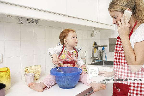 Kleines Mädchen sitzt auf dem Küchentisch  während ihre Mutter mit dem Smartphone telefoniert.