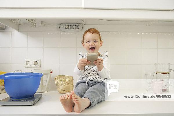 Lachendes kleines Mädchen sitzend auf der Küchenzeile mit Smartphone