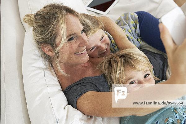 Glückliche Mutter  Tochter und Sohn auf der Couch  die einen Selfie nehmen.