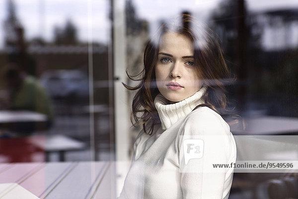 Porträt einer jungen Frau  die durch die Fensterscheibe eines Cafés schaut.